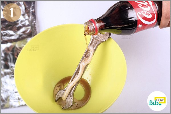 Pour Coca Cola on rusty tools in bowl