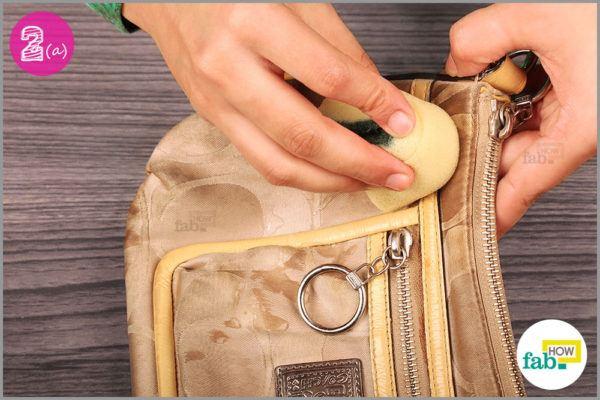 Gently rub the sponge on bag