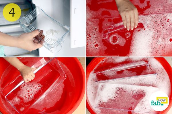 Detach shelves and trays and soak them in soapy solution