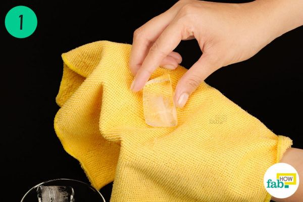 Wrap an ice cube in a towel