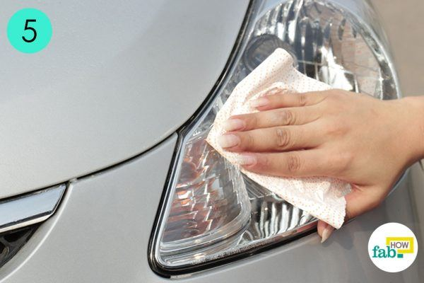 clean car headlight with clean paper towel