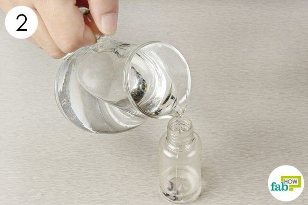pour water into a spray bottle for cleaning with baking soda