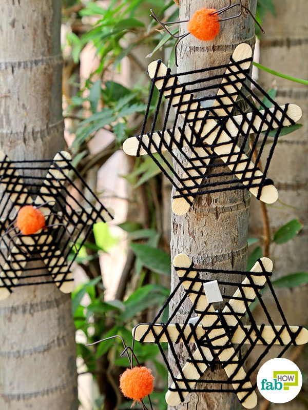 Hang the DIY popsicle spider webs outside your door on on the trees
