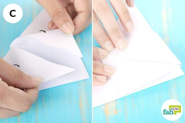 Fold the bottom corners to meet at the triangle tip